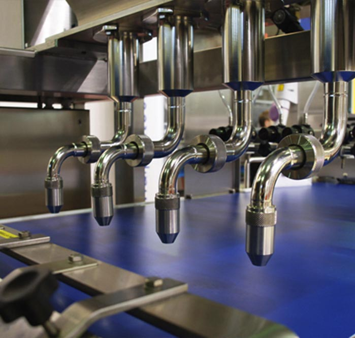 coating spray nozzles attached to machinery over conveyor