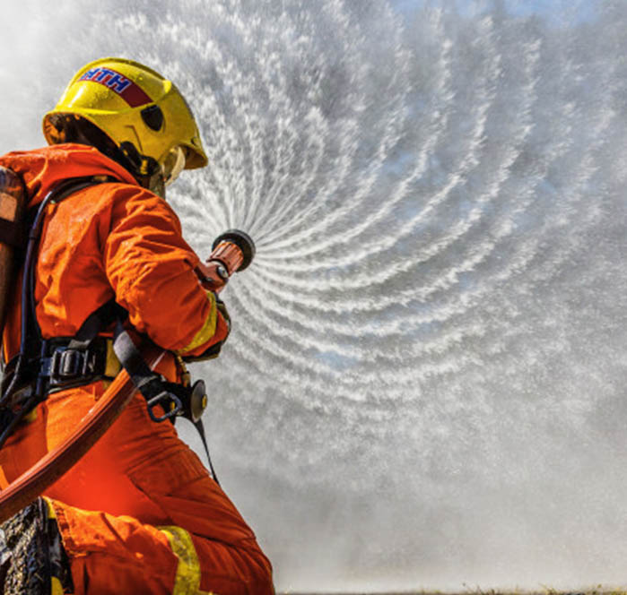 fire fighter with adjustable hand nozzle spraying water